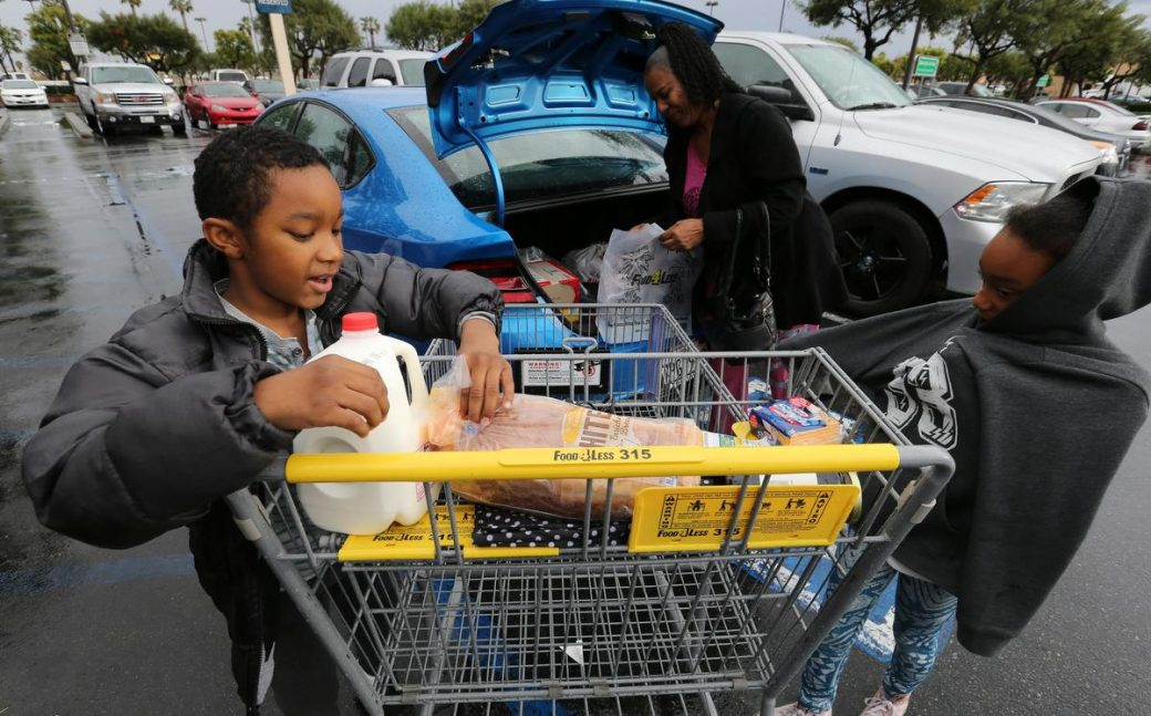 Kavon Ransom, 9, and Kayla Waters, 10, help their grandmother Lois Worthy load the groceries in the car after shopping at the Food 4 Less in Perris Thursday, Dec. 22, 2016. FRANK BELLINO, THE PRESS-ENTERPRISE/SCNG